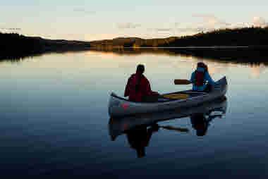 Par i kanot på spegelblank sjö paddlar genom skogslandskap